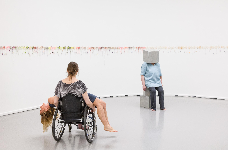 Frau mit Rollstuhl und liegender Person auf dem Schoß in der Ausstellung