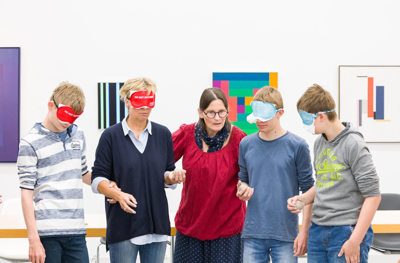 Workshop-Leiterin führt 4 Menschen mit verbundenen Augen