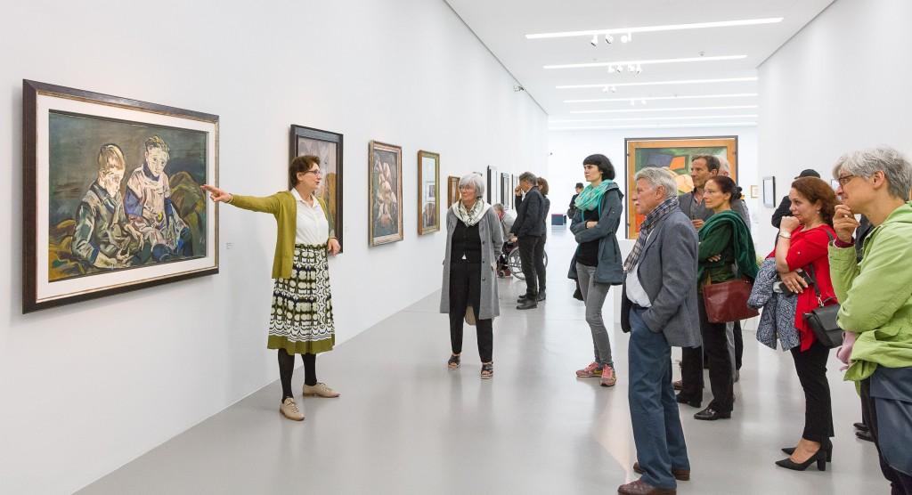 Menschen stehen vor Gemälden