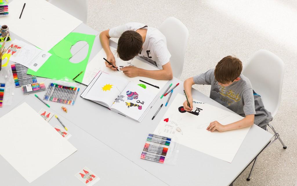 Kinder malen an einem Tisch
