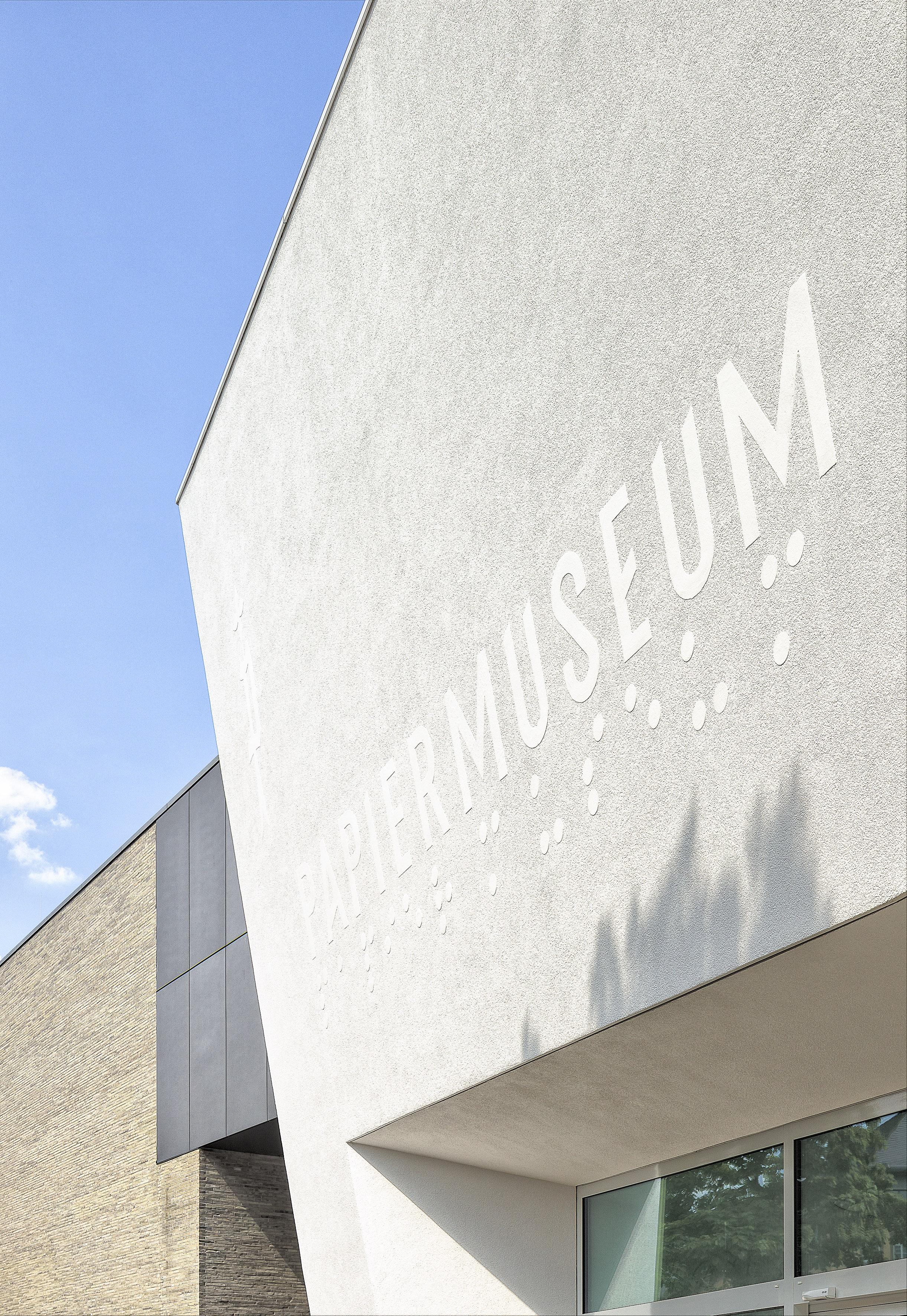 """Fassadenschrift """"Papiermuseum"""" weiß auf weiß über dem Eingangsbereich"""