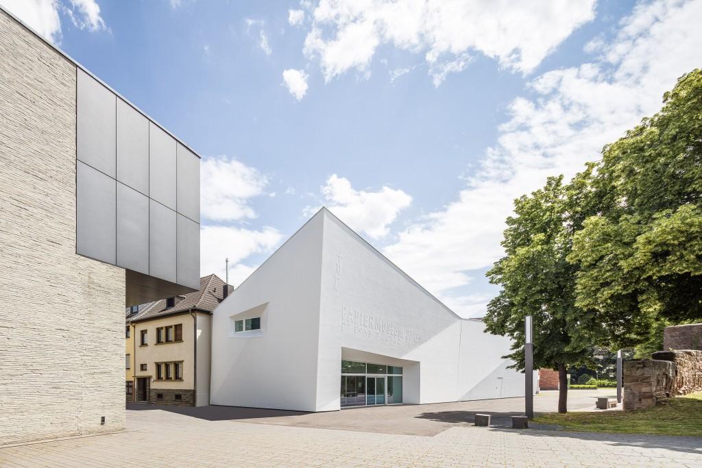 Außenansicht des Papiermuseums Düren mit dem Erweiterungsbau des LHM links und der historischen Stadtmauer rechts